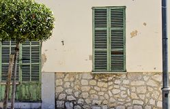 Green house in Majorca. Painted doors and windows houses on the main street in , Majorca, Spain Royalty Free Stock Photography