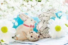 Painted Easter bunnies with white daisies and colored eggs, selective focus royalty free stock photo