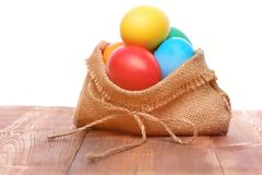 Painted easter colorful eggs in burlap sack  on white Stock Photo