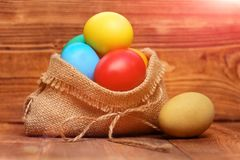 Painted easter colorful eggs in burlap sack on wooden background Stock Photography