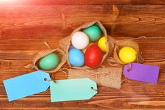 Painted easter colorful eggs in burlap sack on wooden background Stock Photo