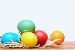 Painted easter colorful eggs with straw nest isolated on white Royalty Free Stock Image