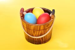 Painted easter colorful eggs in wooden bucket on yellow background. Easter egg. funny holiday bunny rabbit and eggs easter colorful eggs painted in bright colors stock photo