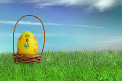 Painted Easter egg in a basket. On grass with sky background Royalty Free Stock Image