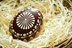 Painted easter egg in a basket with straw, easter background Stock Images