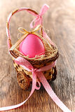 Painted Easter Egg with bow in decorated basket. Painted Easter Egg pink with bow in decorated basket on wooden background Royalty Free Stock Photo
