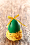Painted Easter Egg with bow in nest on wooden background. Painted Easter Egg green with bow in nest on wooden background Royalty Free Stock Photos