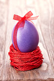 Painted Easter Egg with bow in nest on wooden background Royalty Free Stock Image