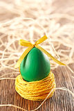 Painted Easter Egg with bow in nest on wooden. Painted Easter Egg green with bow in nest on wooden background Royalty Free Stock Image