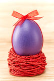 Painted Easter Egg with bow in nest on wooden. Painted Easter Egg purple with bow in nest on wooden background Stock Photography