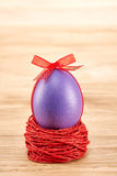 Painted Easter Egg with bow in nest on wooden. Painted Easter Egg purple with bow in nest on wooden background Royalty Free Stock Photo