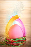 Painted Easter Egg in colorful nest on wooden. Painted Easter Egg in colorful straw nest with feathers on wooden background Stock Photos
