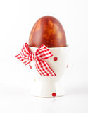 Painted Easter egg in the egg cup on the white background Royalty Free Stock Image