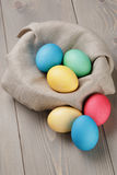Painted easter eggs in basket on wood table Royalty Free Stock Images