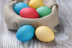 Painted easter eggs in basket on wood table Royalty Free Stock Image