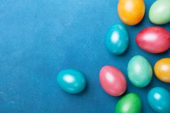 Painted Easter eggs on blue table top view. Holiday greeting card. royalty free stock photo