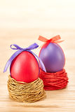 Painted Easter Eggs with bow in nests on wooden. Painted Easter Eggs purple and red with bow in nests on wooden background Stock Images