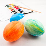 Painted easter eggs brush and palette. One orange, one green and a half painted blue easter egg with watercolor palette and brush in background royalty free stock photos