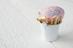 Painted Easter eggs in a bucket on a white wooden table, text co Royalty Free Stock Images