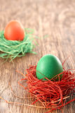Painted Easter Eggs in colorful nests on wooden background. Painted Easter Eggs in colorful straw nests on wooden background Royalty Free Stock Image
