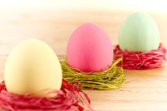 Painted Easter Eggs in colorful nests on wooden background. Painted Easter Eggs in colorful straw nests on wooden background Stock Images