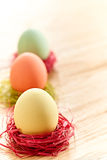 Painted Easter Eggs in colorful nests on wooden background. Painted Easter Eggs in colorful straw nests on wooden background Royalty Free Stock Photos