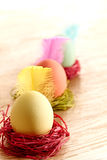 Painted Easter Eggs in colorful nests on wooden background. Painted Easter Eggs in colorful straw nests with feathers on wooden background Royalty Free Stock Photography