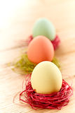 Painted Easter Eggs in colorful nests on wooden. Painted Easter Eggs in colorful straw nests on wooden background Royalty Free Stock Images