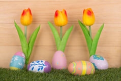 Painted Easter Eggs. Colorful painted Easter eggs with tulips against a wood background Stock Photos