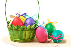 Painted Easter Eggs in decorated Basket on white background. Painted Easter Eggs with bows in decorated green Basket on white background Royalty Free Stock Photo