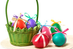 Painted Easter Eggs in decorated Basket on white background. Painted Easter Eggs with bows in decorated green Basket on white background Stock Image