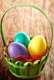 Painted Easter Eggs in decorated basket on wooden background. Painted Easter Eggs pink in decorated green basket with straw on wooden background Royalty Free Stock Images