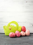 Painted Easter Eggs  in decorated green basket on wooden table. Stock Images