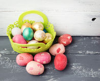 Painted Easter Eggs  in decorated green basket on wooden table. Royalty Free Stock Images