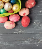 Painted Easter Eggs  in decorated green basket on wooden table. Royalty Free Stock Photo
