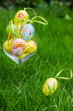 Painted easter eggs in glass on green grass Royalty Free Stock Image