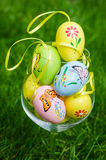 Painted easter eggs in glass on green grass Royalty Free Stock Images