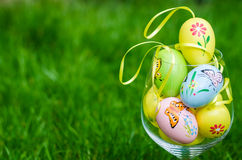 Painted easter eggs in glass on green grass Royalty Free Stock Photo