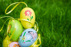 Painted easter eggs in glass on green grass Stock Images