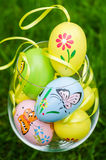 Painted easter eggs in glass on green grass Stock Photography