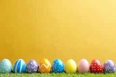 Painted Easter eggs on green grass against color background. Space for text stock photo