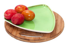 Painted easter eggs on green plate and a kitchen board Royalty Free Stock Photography