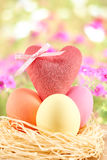 Painted Easter Eggs with Heart in nest on floral. Painted Easter Eggs with Heart in straw nest on floral background Royalty Free Stock Photo