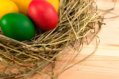 Painted Easter eggs lie in a nest of hay. Easter eggs, painted in green, red, yellow, lie in a nest of hay Royalty Free Stock Photography