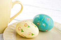 Painted easter eggs on light yellow plate Stock Photos