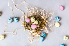 Painted easter eggs lying in nest on gray concrete background. Top view. Flat lay. Holiday concept royalty free stock image