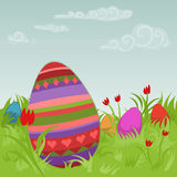 Painted easter eggs on a meadow. Bunch of colorful, painted easter eggs on a beautiful meadow with tulips Stock Photos