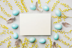 Painted Easter eggs, mimosa flower and paper card on vintage stone background top view in flat lay style. Empty space for text. Stock Photo