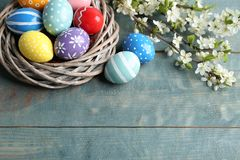 Painted Easter eggs in nest and blossoming branches on table, view from above. Space for text royalty free stock images