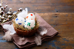 Painted Easter eggs in a nest on napkin Stock Photos